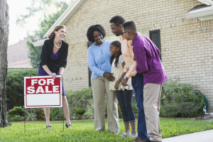 A real estate agent standing in front of a house with a FOR SALE sign in the yard, with an African American family who could be the homeowers, or potential buyers.  The agent is wearing a black jacket and purple dress.