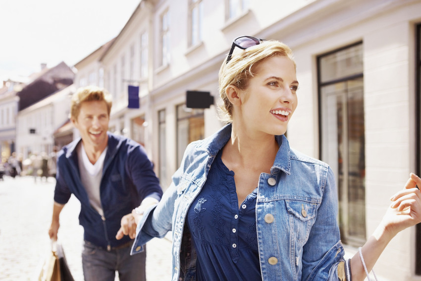 Gorgeous young woman and man walking along shops holding hands