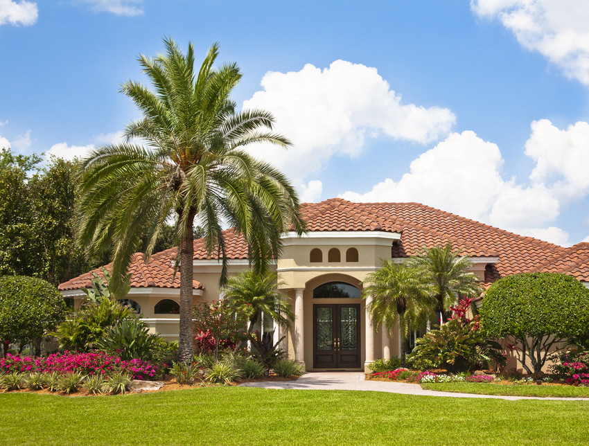 New luxury home with palm trees, flowers, green lawn and lush tropical foliage.